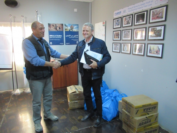 GCSP participants and staff offer gifts for schools at Zaatari Camp